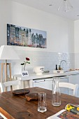 Wooden table, white kitchen counter and large photos