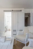 Upholstered chairs in white lounge area with view through sliding door into bathroom