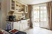 Vintage wall units in country-house kitchen with view onto sunny terrace through lattice windows