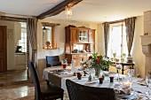 Festlich gedeckter Esstisch mit Blumendeko in ländlichem Esszimmer mit Durchgang zur Küche