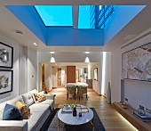 Illuminated living room with skylight at twilight