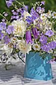Blau-weißer Blumenstrauß in einer Emaillekanne auf dem Gartentisch