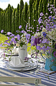 Vases of flowers on garden table festively set in blue and white