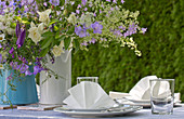 Vases of purple and white flowers on festively set garden table