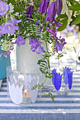 Candle lanterns decorated with paper bellflower silhouettes in front of vase of flowers