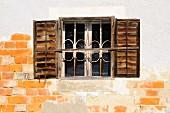 Altes Fenster mit Gittern und Fensterläden an maroder Fassade