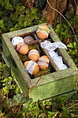 Undyed Easter eggs with lace trim and delicate satin ribbons on moss in vintage wooden crate