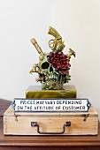 Skull and flower sculpture with sign on old wooden case