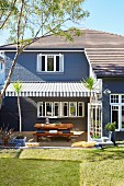 House with garden and patio under a striped awning