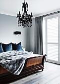 Fur blanket on an old wooden bed under a black chandelier