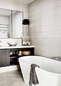 Freestanding bathtub in modern bathroom in shades of gray