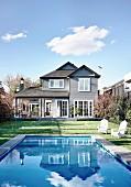 Haus und blauer Himmel spiegeln sich im Swimmingpool im Garten