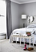 Upholstered bench in front of the bed in the bedroom in shades of gray
