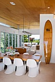 Open kitchen with elegant dining area, ajar surfboard and window front