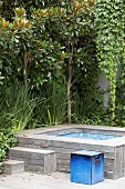 Garden corner with green plants and wood-clad water basin