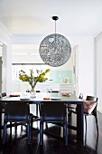 Ball lamp over black dining table in front of open kitchen