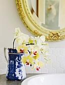 Gelbe Orchideen in blau-weißem Krug auf Waschtisch, darüber Spiegel mit geschnitztem Rahmen