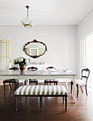 Upholstered bench and chairs in front of antique table in dining room with oval mirror on wall in background