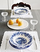 Place setting with blue and white crockery on place mat and apricots on white plate
