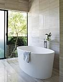 Modern free-standing bathtub with view into garden