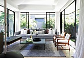 Living room with glass walls leading to summery garden