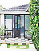 Open front door in porch with glass walls and chequered floor