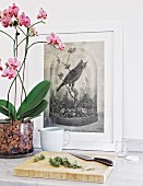Rosemary on chopping board next to orchid and picture