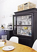 Black glass-fronted cabinet behind dining area in kitchen