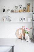 Storage jars and crockery on white shelves above kitchen counter