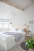 Double bed with wooden headboard in bright attic bedroom