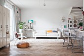 Herringbone parquet floor and white couch next to shabby-chic table in open-plan interior
