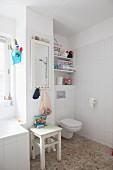 Weisses Bad mit Kieselsteinboden, Toilette, Holzhocker und Wandspiegel