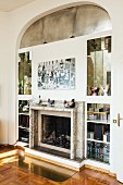 Masonry shelves with mirrored niches surrounding open fireplace