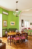 Dining table, wooden chairs and green walls in front of open doorway leading into living room
