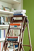 Books stacked on wooden ladder in front of bookcase