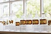 Aufgereihte Apothekergläser mit Etiketten vor dem Fenster