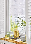 A romantic lace curtain in a window with decorative plants on the window sill