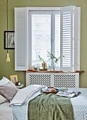 A breakfast table on a bed and in front of a window with a sliding white curtain in a green-painted bedroom