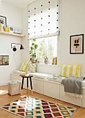 weiße, massgefertigte Sitzbank mit Schubladen und Sitzpolster in heller Zimmerecke vor Fenster