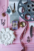 Mood board with film reel and knick-knacks on pink surface