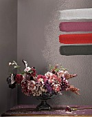 Vase of flowers spattered with paint and paint samples on wall; photographic art