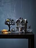 Gespenstisches Deko-Häuschen mit Baum, Grab und schwarzer Katze als Halloweendeko