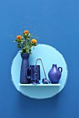 Ceramic vessels and flowers on wall-mounted shelf in pale blue circle on rich blue wall