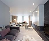 Grosszügiger Wohnraum mit Sessel und Sofa vor Fenster und luftigen Vorhängen, im Vordergrund Polstersofa
