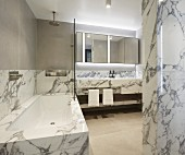 Marble-clad bathtub and washstand and backlit mirrored cabinet in luxurious bathroom