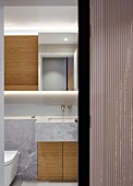 Marble-clad washstand with custom wooden base cabinets seen through half-open sliding door