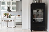 Black display cabinet in front of open-plan kitchen with dining area