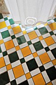 Multicoloured geometric tiled floor and white curtain with spiral motif