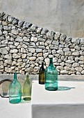 Arrangement of bottles in front of stone wall outside