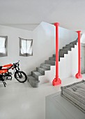 Concrete staircase behind red, industrial-style steel column and motorbike on pale concrete floor
